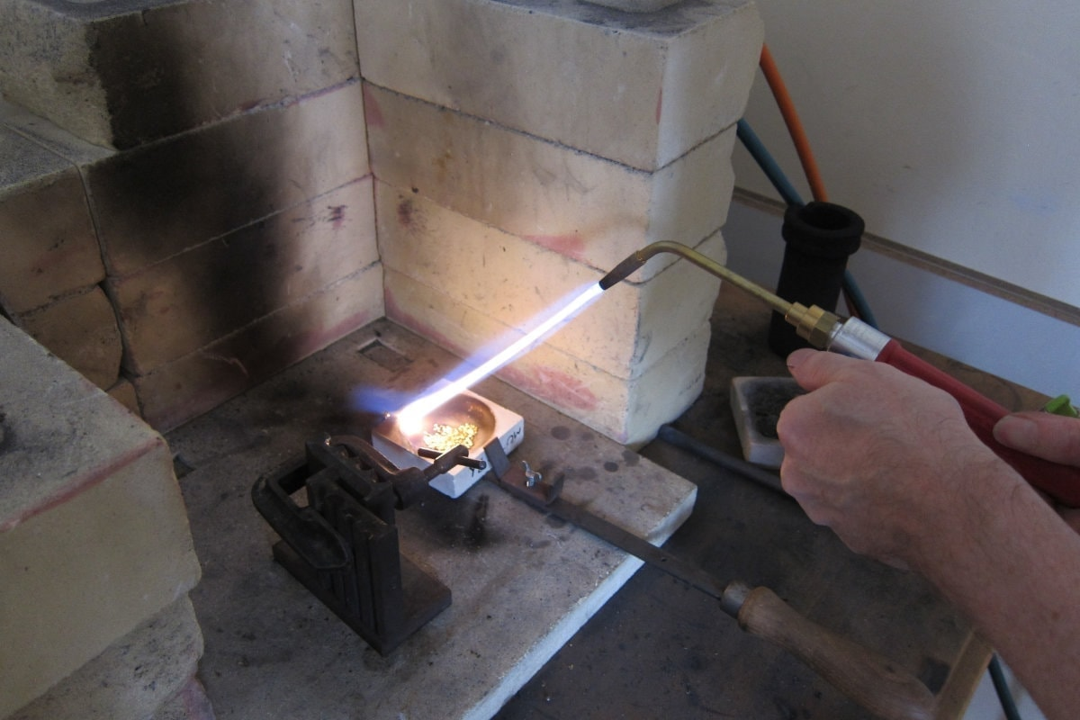 Torch using gas and air mix to melt the grains in the crucible.