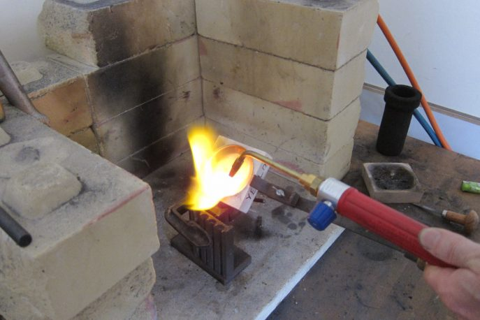 Gold grains are melted the liquid is poured into a mould to make a gold ingot.